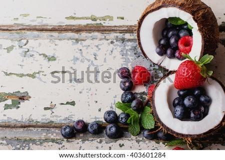 Organic berries: blueberries and strawberries served in two coconuts on a light wooden rustic, background. Concept of healthy food. Top view. Selective Focus - stock photo