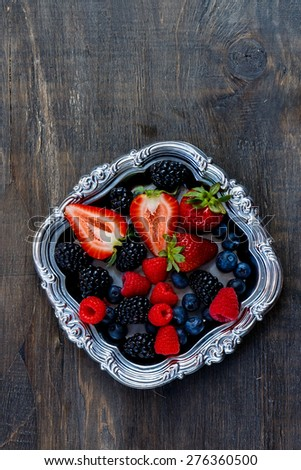 Organic berries on vintage metal plate over dark wooden background. Agriculture, Gardening, Harvest Concept. - stock photo