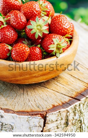 Organic Berries Strawberries Closeup. Ripe Strawberry In Fruit Garden, Old Wooden Bowl Filled With Succulent Juicy Fresh Ripe Red Strawberries On Old Birch Stump - stock photo