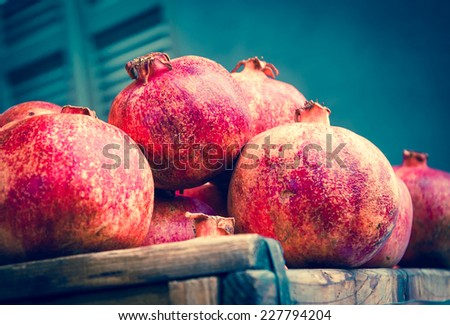 Organic bio pomegranate fruits in wooden boxes at the farmers market. Pomegranate is one of Rosh Hashana (Jewish New Year) symbols. Still life. Closeup. Selective focus. Aged photo. - stock photo