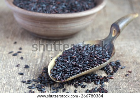 Organic Black Nerone Rice in a scoop on a wooden table,  selective focus - some grains in focus, some are not - stock photo