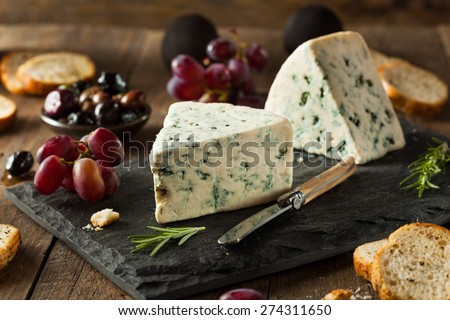 Organic Blue Cheese Wedge with Olives and Grapes - stock photo