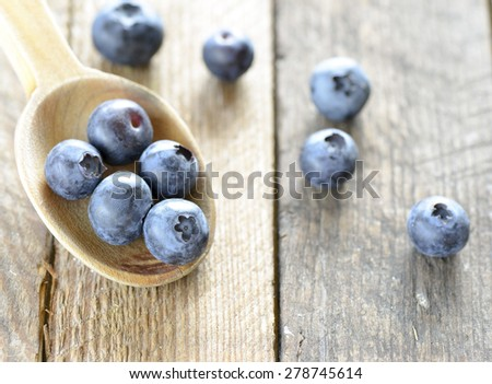 Organic blueberries in spoon. Organic blueberries in spoon on wooden background. - stock photo