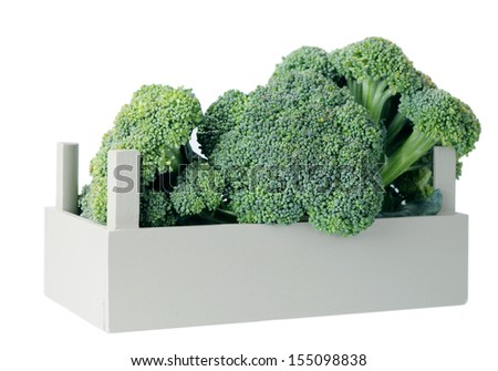organic broccoli in crate against white background  - stock photo