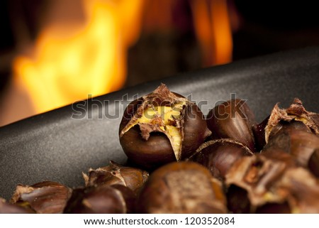 Organic Brown Chestnuts Roasting over a hot fire - stock photo