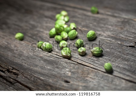 Organic brussels sprouts on a rustic wooden board - stock photo