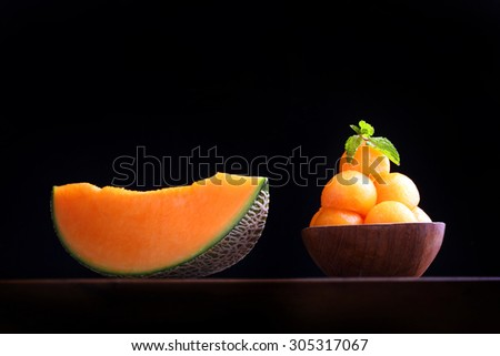 Organic cantaloupe melon in wooden bowl isolated on black background.