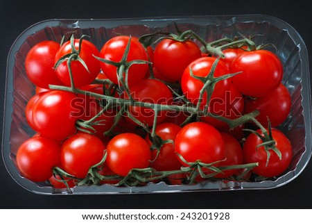 Organic cherry tomatoes in a plastic box on black background.