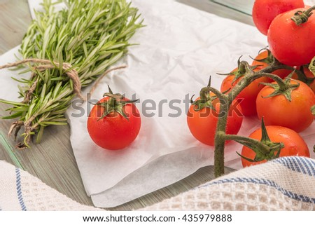 Organic cherry tomatoes with rosemary on wrinkled paper - stock photo