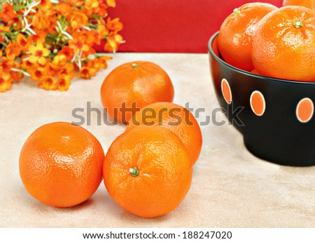 Organic clementines on a table with a full bowl of orange fruit to the side. - stock photo