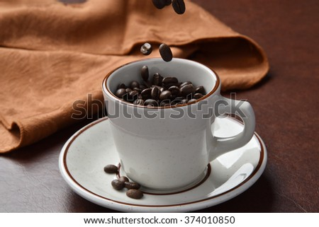 Organic coffee beans pouring into a cup - stock photo