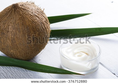 organic cosmetic cream and coconut on white wooden  - stock photo