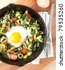Organic Egg Fried in Middle of Sauteed Vegetables on Cast Iron Skillet - stock photo