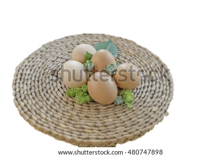 organic egg with small green plant on bamboo mat with white background