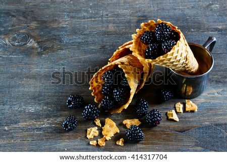 Organic fresh blackberries in waffle cones served on dark wooden textured background, space for text, selective focus. - stock photo