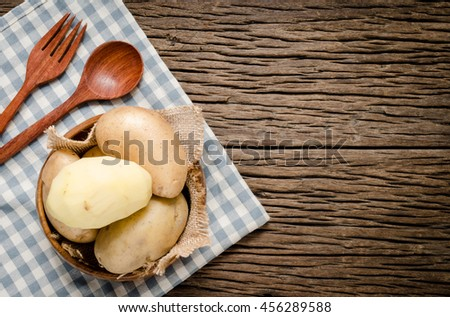 Organic fresh potatoes in wooden bowl with fabric background. Raw organic potato on old wooden background. - stock photo