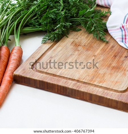 Organic fresh vegetables and rustic cutting board on a white table. Ingredients for spring soup. Selective focus, outdoor background - stock photo