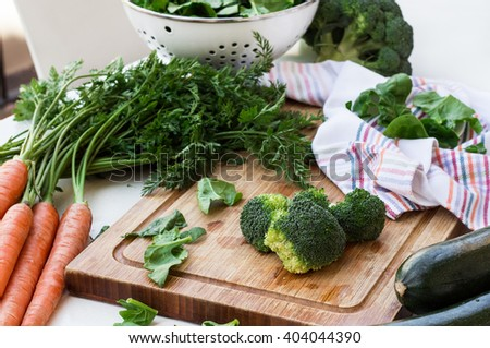 Organic fresh vegetables on a cutting board on a white table. Ingredients for spring soup. Selective focus - stock photo