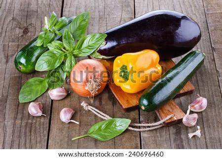 Organic fresh zucchini, eggplant, yellow capsicum, garlic and basil over rustic wooden background - stock photo