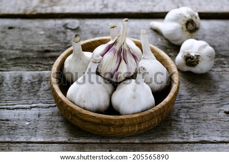Organic garlic in a wooden bowl on the wooden table - stock photo