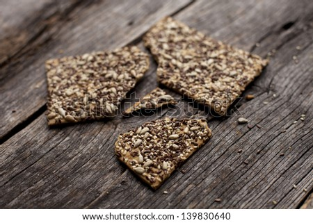 Organic gluten free buckwheat crackers on a rustic wooden board - stock photo