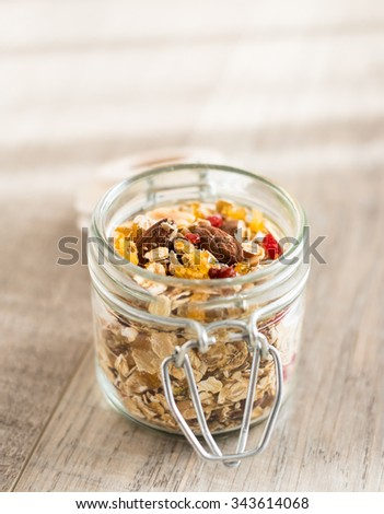 Organic granola with oat flakes, goji berries, almond nuts in a jar on the wooden table, selective focus - stock photo