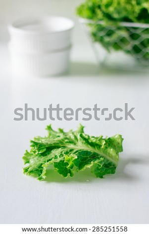 organic green lettuce prepare for cooking, fresh lettuce on white wood table. Image soft focus.
