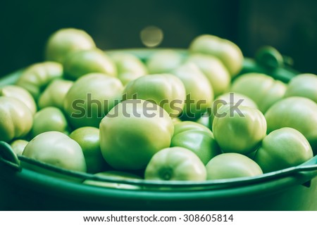 Organic green tomato in plastic bucket. Macro image. - stock photo