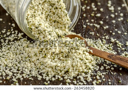 Organic hemp seeds spilling out of glass jar with measuring spoon on wooden table - stock photo