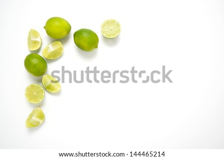 Organic Limes Whole and Halved on White Table - stock photo