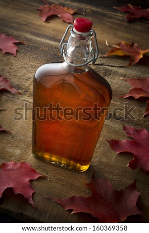 Organic maple syrup on wooden background with maple leaves - stock photo