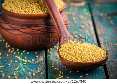 organic millet seeds in a spoon and a ceramic bowl closeup on wooden table - stock photo