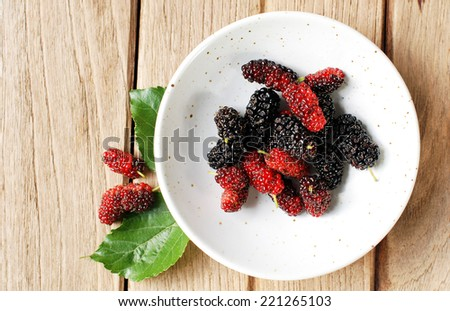 organic mulberry in plate on wooden background.