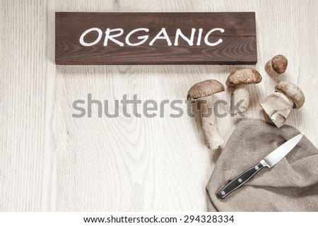 Organic mushrooms on the wooden table with knife