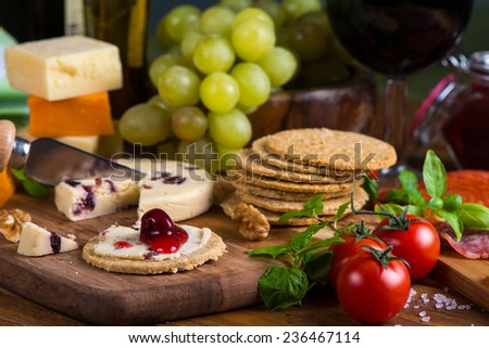 Organic oat crackers with cheese basil and red wine - stock photo
