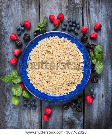 Organic oatmeal in blue bowl with summer berries on wooden background, top view - stock photo