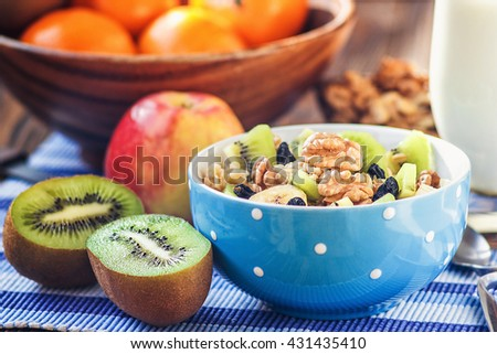 Organic oatmeal porridge in ceramic bowl with bananas, honey, walnuts, kiwi fruit and raisins. Healthy breakfast - health and diet concept on the wooden table, close up - stock photo
