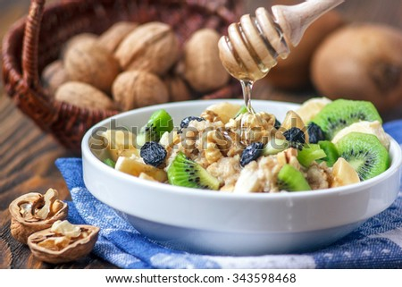 Organic oatmeal porridge in white ceramic bowl with bananas, honey, walnuts, kiwi fruit and raisins. Healthy breakfast - health and diet concept on the wooden table, close up. - stock photo
