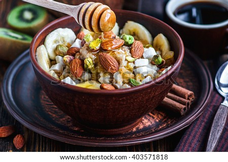 Organic oatmeal porridge with bananas, honey, almonds, pistachio, coconut, kiwi fruit, cinnamon, raisins in dark ceramic bowl  and cup of coffee. Healthy breakfast and diet concept on wooden table. - stock photo