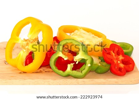Organic paprika peppers with slice over wooden table - stock photo
