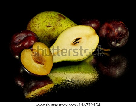 organic pear and plum on a black background with water drops - stock photo
