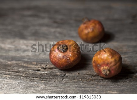 Organic pomegranates on a rustic wooden board - stock photo