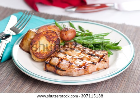 organic pork chop with pan sauteed potatoes and green beans with a peach sauce