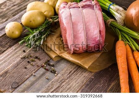 Organic pork lion roast with rosemary on wood farm table. - stock photo