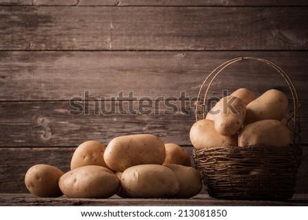 organic potatoes on wooden background - stock photo