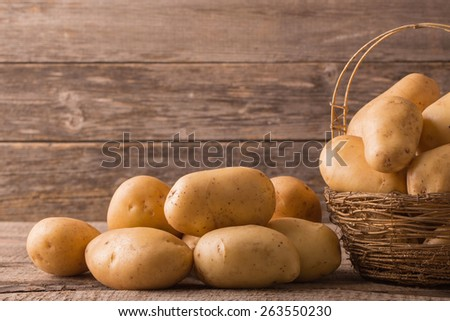 organic potatoes on wooden background - stock photo