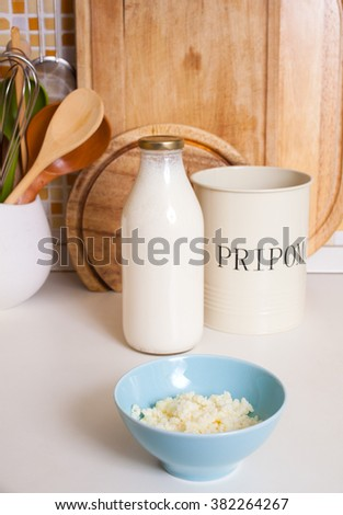 Organic probiotic milk kefir grains inside the bowl. The word Pripomocki in the iron bowls in english is flatware container