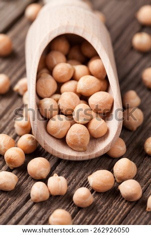 Organic raw chickpeas healthy vegan nutrition super food in wooden spoon - stock photo