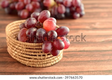 Organic Raw Red Grapes in a Basket on Wooden Background - stock photo