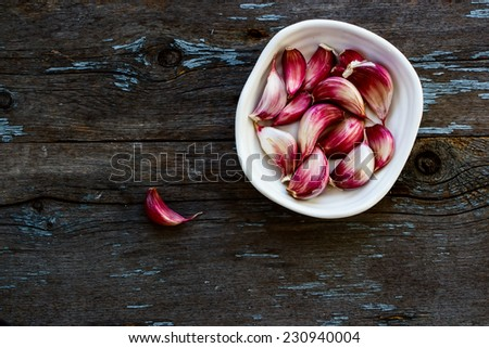 Organic red garlic cloves in a white bowl on the vintage wooden table, top view - stock photo